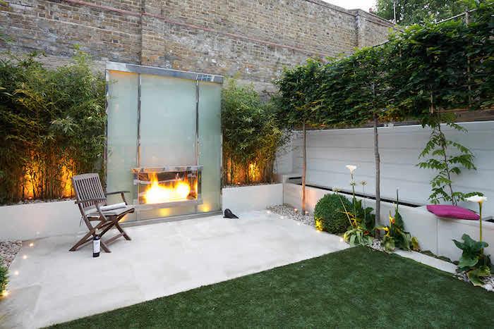 cheminée extérieure, clôture aluminium, briques et bambou, gazon vert, et espace béton avec chaise bois