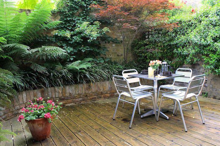 amenagement terrasse exterieure en bois avec un mur de cloture en briques envahis par la végétation