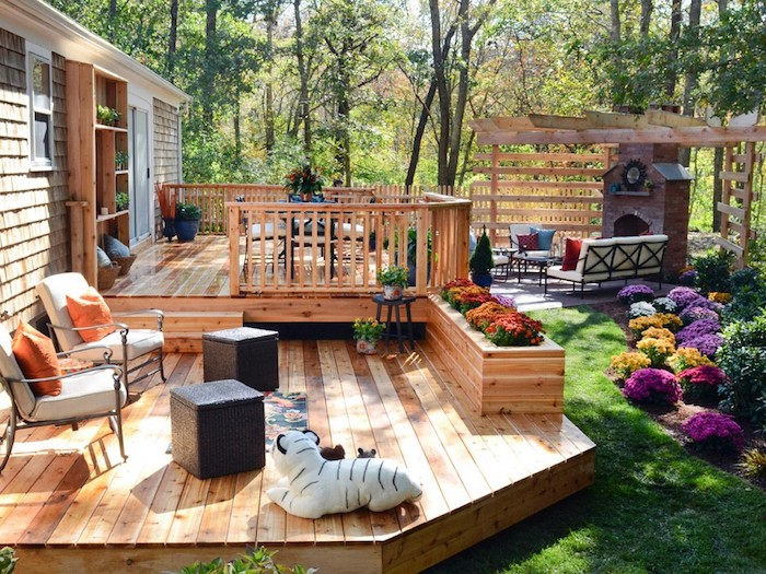 idée terrasse bois moderne à plusieurs niveaux, amenagement en table et chaises avec un coin repos doté de cheminée, canapé et chaises métalliques et pergola bois