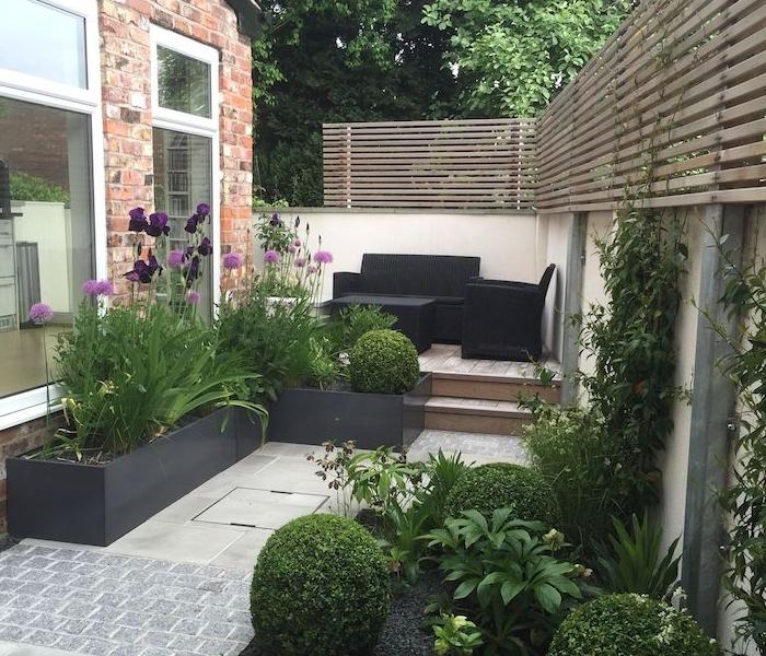 decoration jardin terrasse en bois avec salon de jardin en mobilier noir, bacs à fleurs noirs, buis taillés et autres fleurs