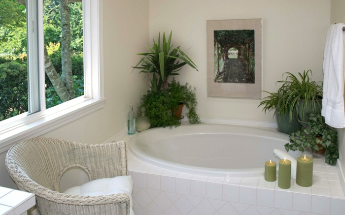 plantes d'appartement, petite salle de bain, pots posés sur les bords de la petite baignoire ovale blanche, trois grandes bougies vertes, fauteuil en rotin blanc, baignoire revêtue en carrelage blanc, grande fenêtre près de la baignoire