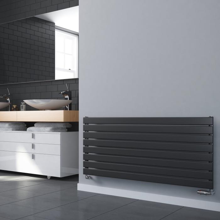 modèle de radiateur salle de bain de couleur gris foncé sur un pan de mur gris clair, carrelage design briques en gris foncé