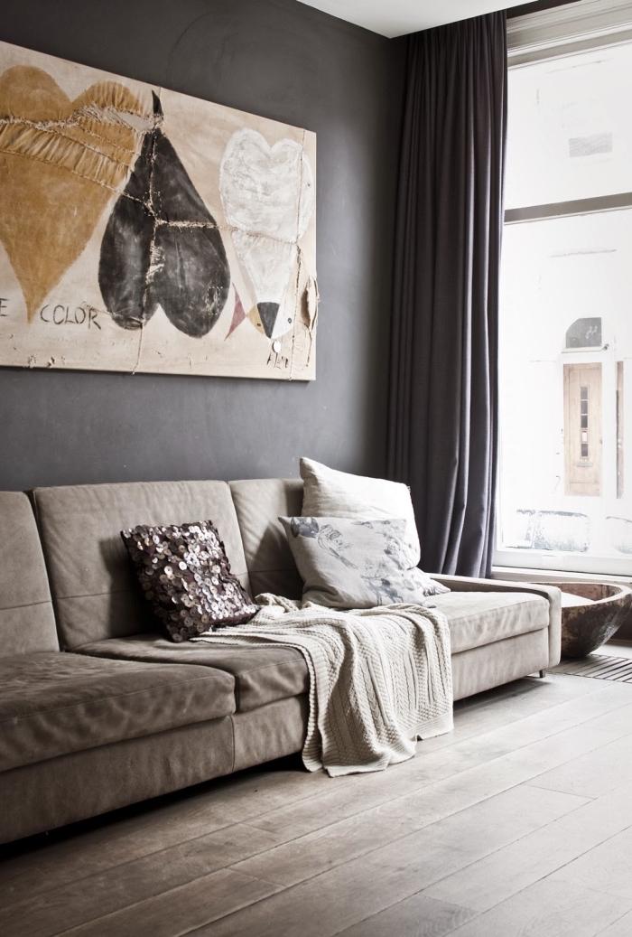 aménagement de salon avec grande fenêtre et murs foncés, modèle de canapé long de couleur beige sur un parquet de bois foncé
