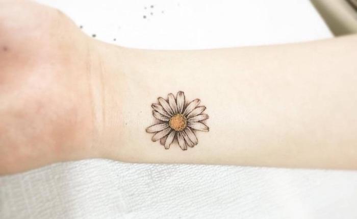 joli modèle d'un tatouage simple à design floral, dessin en encre avec marguerite tatoué sur le poignet