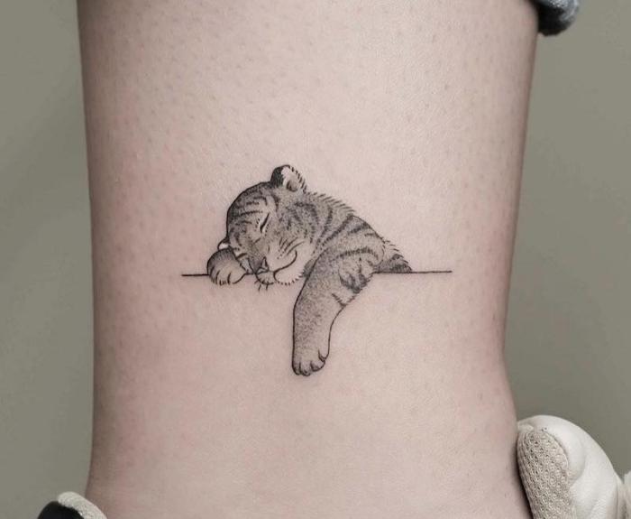 mini tigre endormi dessiné en encre sur la jambe, modèle de mini tattoo mignon aux motifs animaux pour homme et femme
