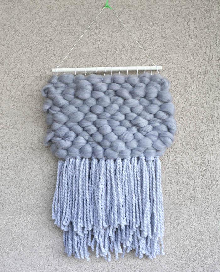 macramé tissé en laine bleue avec reliefs et franges sur mur crépis gris