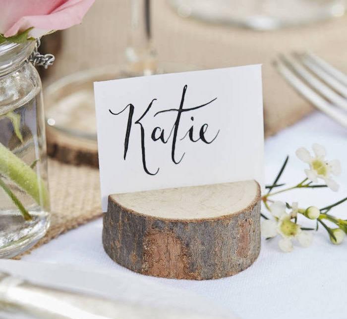 rondelle de bois incisé avec une étiquette nom invité sur un bout de carton blanc, chemin de table en jute