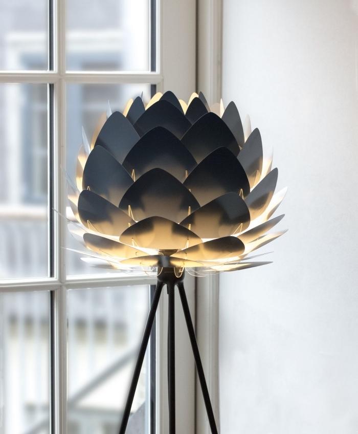 modèle de lampe moderne à design fleur origami en couleur anthracite avec pieds noirs devant une fenêtre blanche