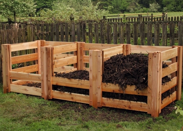modèle de composteur palette de bois laqué construit en forme rectangulaire divisés en trois sections dans le jardin