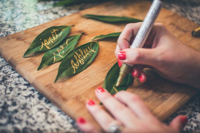 marque place mariage en feuilles vertes avec écriture feutre or nom de l invité, décoration de table florale originale