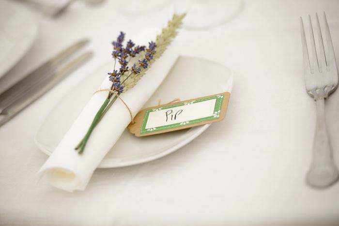 anneau de serviette en étiquette prénom et brin de lavande dans une assiette blanche, nappe blanche, couverts de table argent
