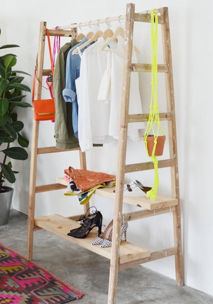 porte manteau design sur pied, échelle en bois avec des planches de bois comme étagères de rangement chaussures, sol gris et tapis coloré, cintres suspendus sur poteau en bois