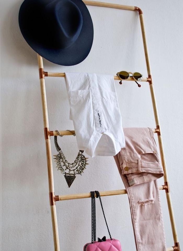 une échelle de bois de bambou et cuivre avec des vêtements, accessoires et bijoux rangés, adossé sur un mur