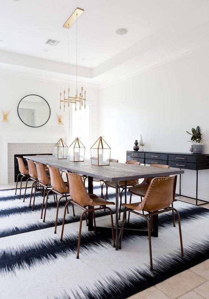table à manger scandinave avec chaises en cuir marron rétro dans salle blanche sur tapis blanc noir