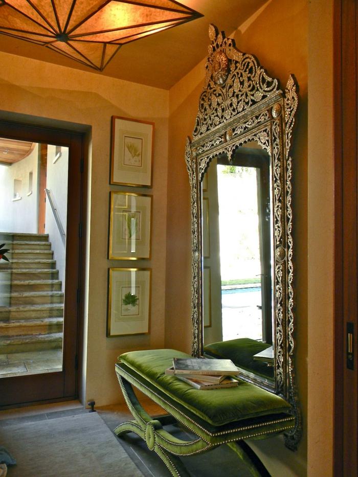 miroir entrée victorien, banquette verte, peinture murale ocre, tableaux encadrés, luminaire design géométrique, banquette moelleuse vert émeraude