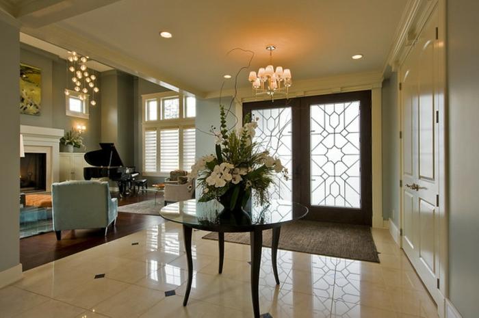 grande entrée lumineuse en couleurs claires, table noire baroque, fauteuil bleu, piano et sol en carrelage blanc