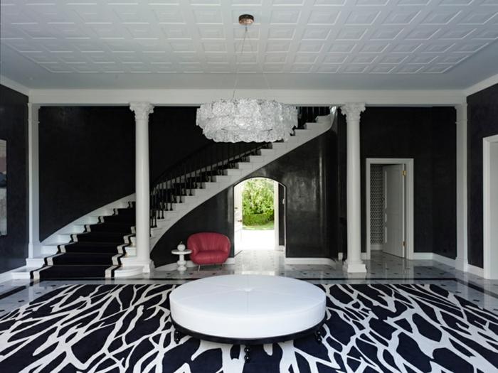 table ronde blanche, sol en noir et blanc, escalier tournant classy, grand plafonnier blanc