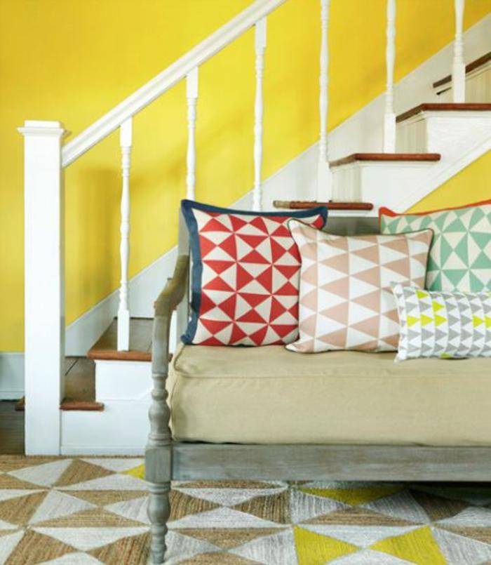 escalier en bois et blanc, mur peint jaune, coussins déco graphiques, tapis graphique