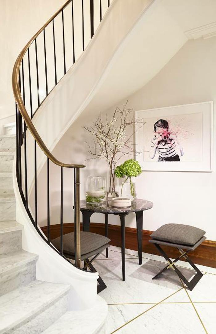 joli escalier tournant dans un hall d'entrée élégant, table avec deux tabourets, peinture artistique