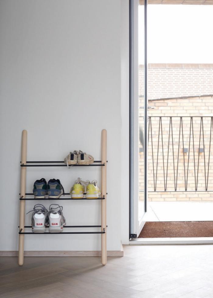 petit meuble chaussure d'esprit minimaliste scandinave en bois et métal, appuyé contre le mur