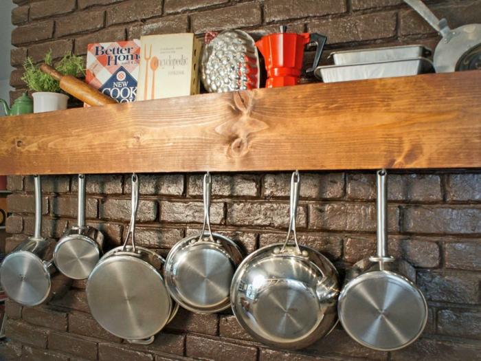 meuble cuisine rangement, casseroles et poêles suspendus sur une etagere cuisine en bois massif, installation sur un mur en briques marron brillantes