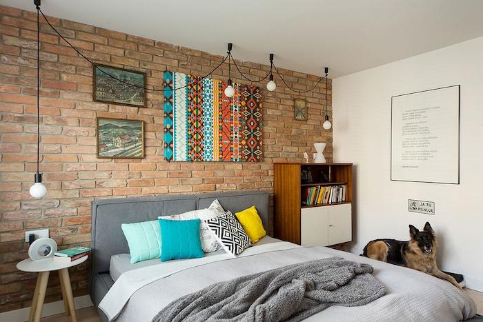 exemple de meuble industriel bois, lit gris, décoré de coussins colorés, linge de lit gris, table de nuit scandinave, mur de briques décoré d art