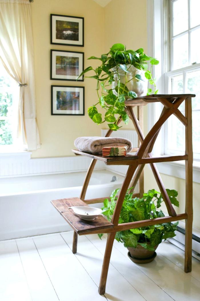 échelle mini avec trois marches en bois marron, sol en bois pvc blanc, baignoire rectangulaire blanche, murs en jaune avec trois tableaux aux cadres noirs, plante salle de bain