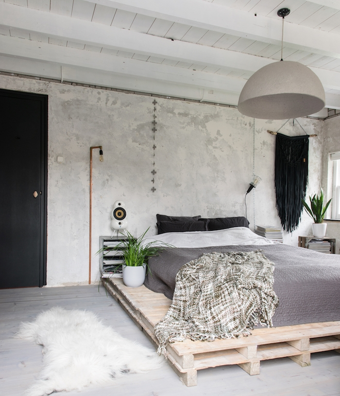 plafond ossature bois apparente, lit en palette avec matelas et linge de lit gris et blanc, mur béton, parquet gris, suspension grise, plante verte