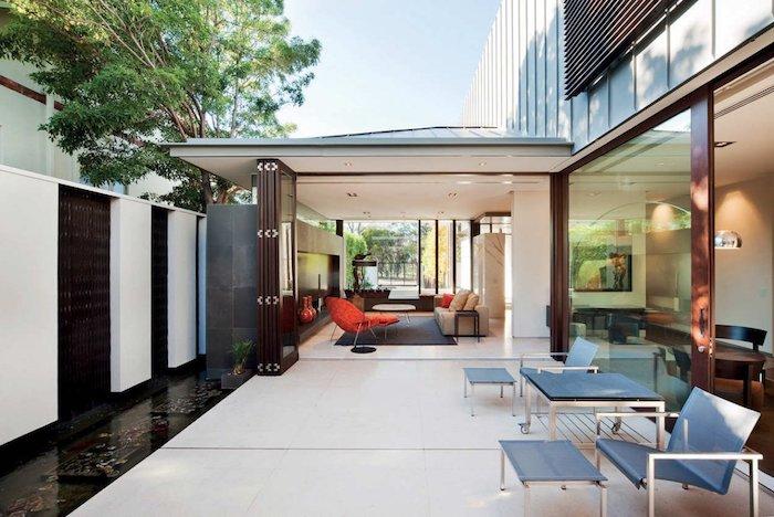 terrasse exterieure moderne avec un coin repos aménagé et composé de table, tabourets et chaises design simple