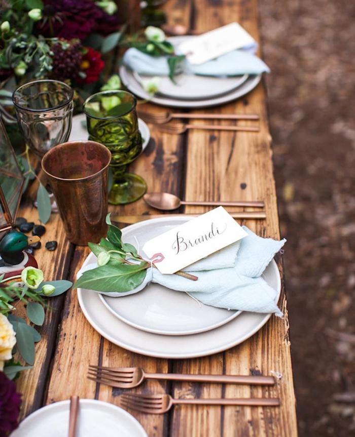 bouquet de feuillages avec une étiquette blanche attachée sur une serviette de table bleu clair sur une table bois brut et centre de table floral