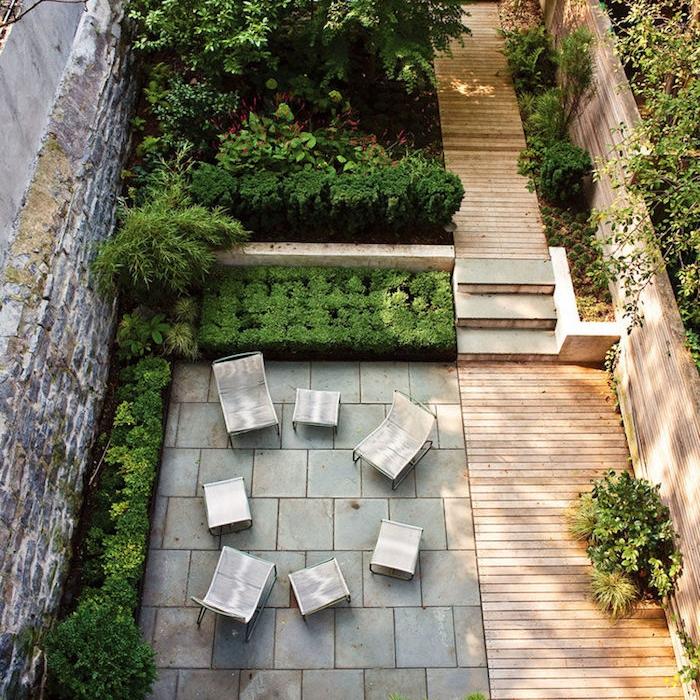 chemin de bois composite et une terrasse moderne en dalles de béton, mobilier de jardin classique, bordures de buis, plusieurs arbustes verts et arbres