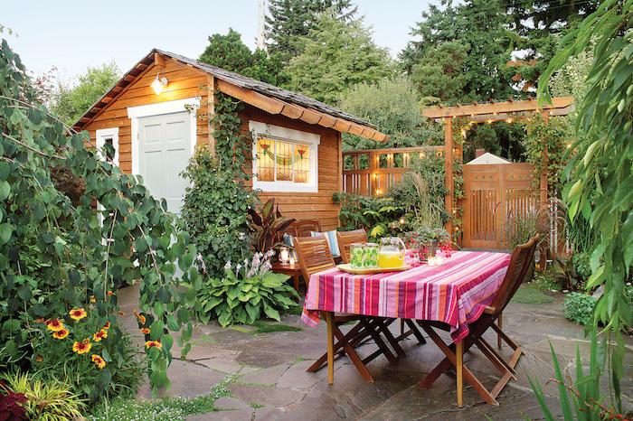 amenagement terrasse exterieure, revetement sol de pierre naturelle dans un jardin avec salle à manger exterieure en chaises et table bois, plantes vertes, petite maison en bois