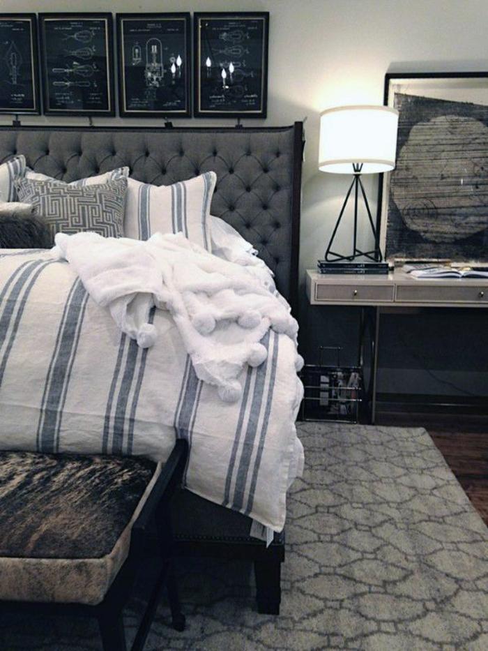 chambre à coucher adulte moderne, tapis géométrique, drap de lit rayé, tête de lit capitonnée, bureau flottant, lampe de table