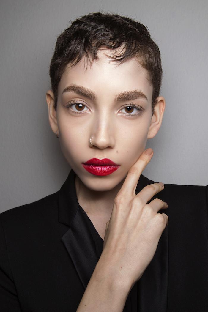 modèle de coupe garçonne simple, cheveux tres courts chatain clair avec quelques mèches ondulés sur le front, tailleur femme noir