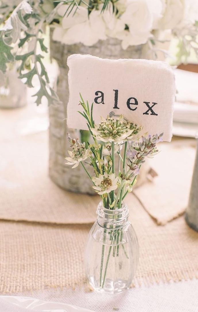 petite bouteille en verre avec un petit bouquet de fleurs à l intérieur avec étiquette prénom invité, chemin de table en jute, centre floral
