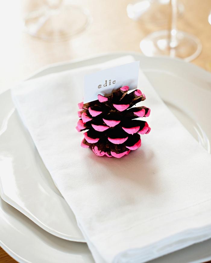 pomme de pin décorée de peinture rose, et etiquette prénom simple, assiettes blanches, deco de table mariage simple