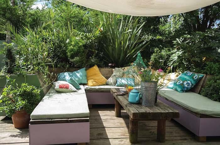 banc en bois, table basse bois brut, coussins décoratifs colorés, entourés d arbustes et arbres vertes, toile d ombrage