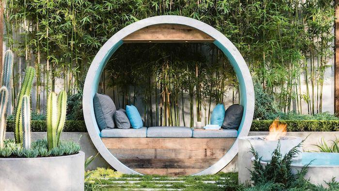 banc en bois avec coussins d assise gris, forme ronde, mur végétal extérieur en bambou, plantes vertes exotiques