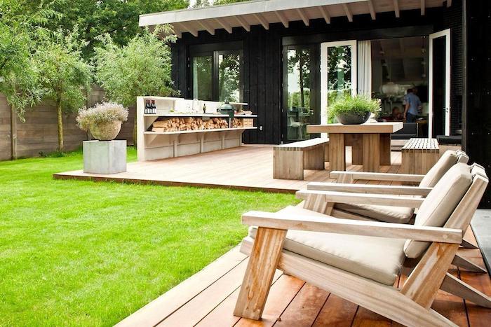 decoration jardin terrasse en bois avec chaise longues bois, gazon vert, table et bancs bois, cadre végétal exotique