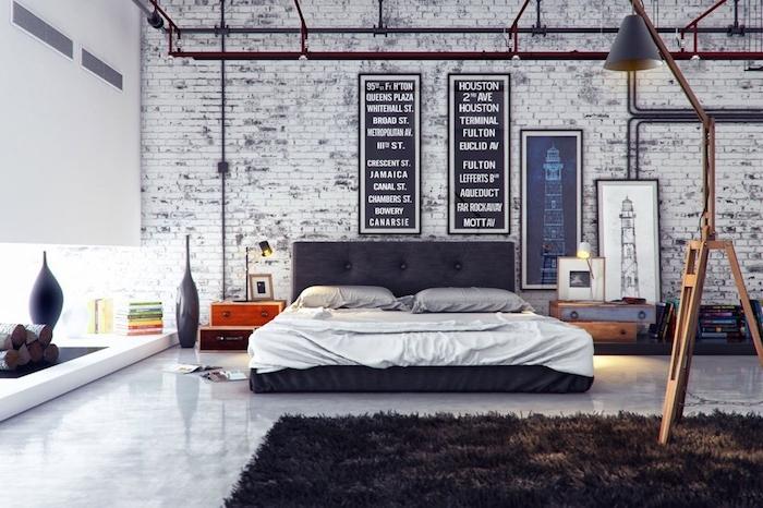 mur de briques gris et blanc, lit gris anthracite avec linge de lit gris et blanc, tapis gris anthracite, deco murale industrielle