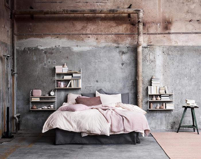 comment faire une etagere industrielle en bois, mur effet béton, tuyaux apparents, linge de lit rose et blanc sur un lit gris, sol gris