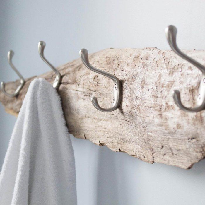 une planche de bois brut avec des accroches montées dessus, porte manteau salle de bain original et facile à faire