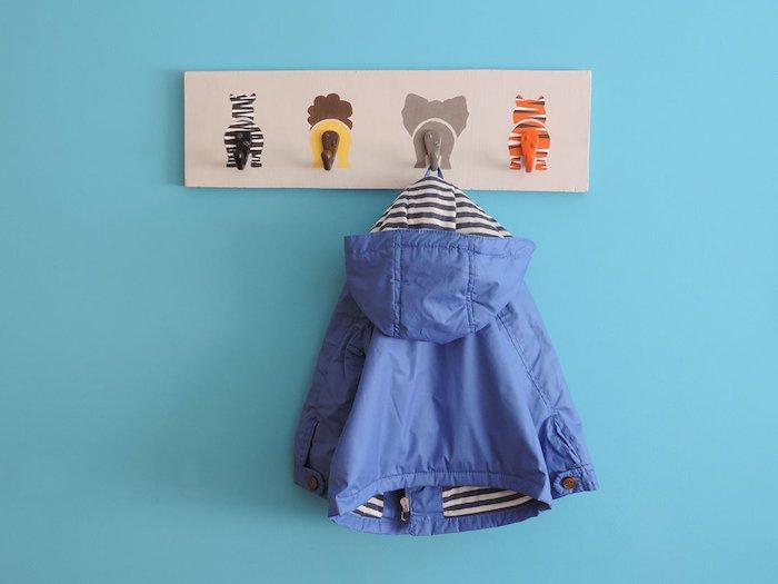 porte manteau mural original pour la chambre à coucher planche de bois avec motif animaux sauvages, mur bleu et blouson enfant
