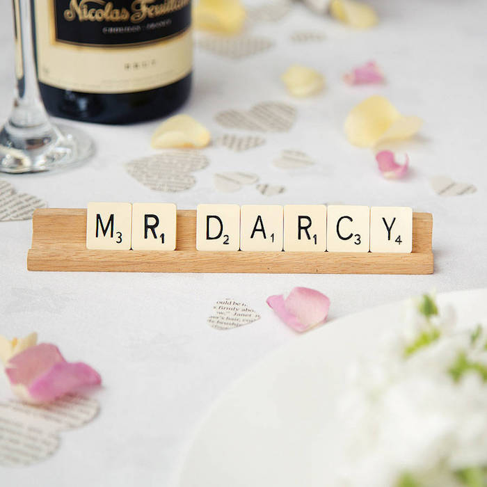 exemple de porte nom de table en bois avec des lettres scrabble pour le nom invité. pétales de rose et coeurs en papier journal