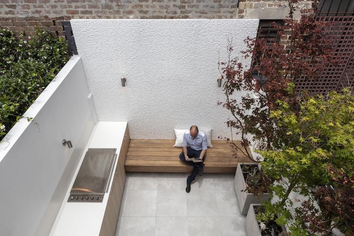 amenagement petite terrasse en dalles de béton, banc en bois, murs blancs, bacs à fleurs en béton avec des arbres plantés dedans