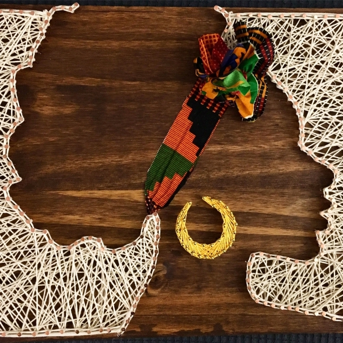 jolie décoration d'intérieur avec un tableau de bois foncé et fil blanc en forme de silhouette femme africaine