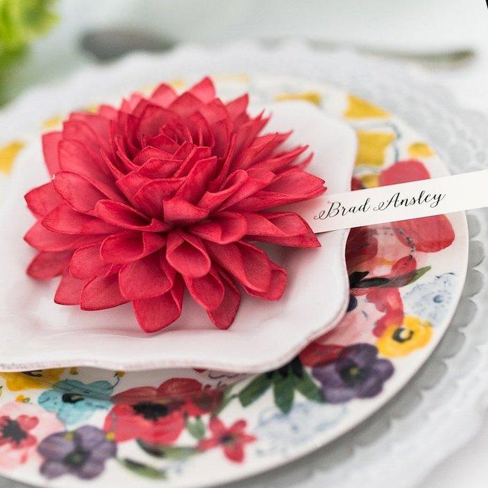 porte nom mariage en fleur de tissu rouge dans assiettes, assiette blanche et assiette fleurie, nom invité sur bout de papier
