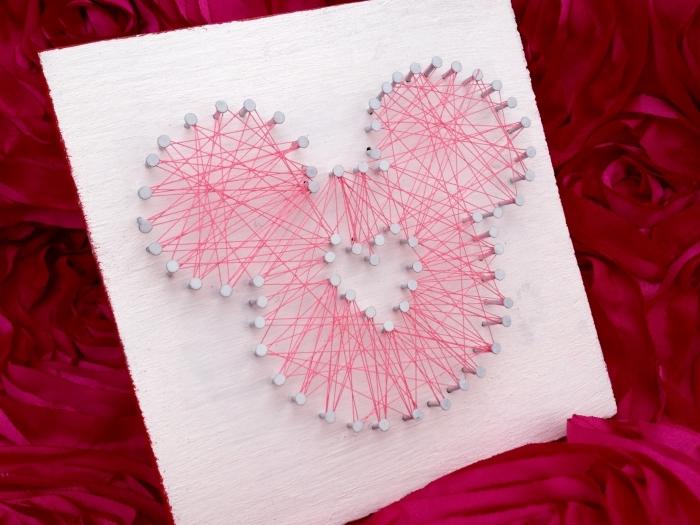 modèle de tableau DIY peint en blanc avec bords rouges et une mignonne décoration en clous et fil tendu rouge