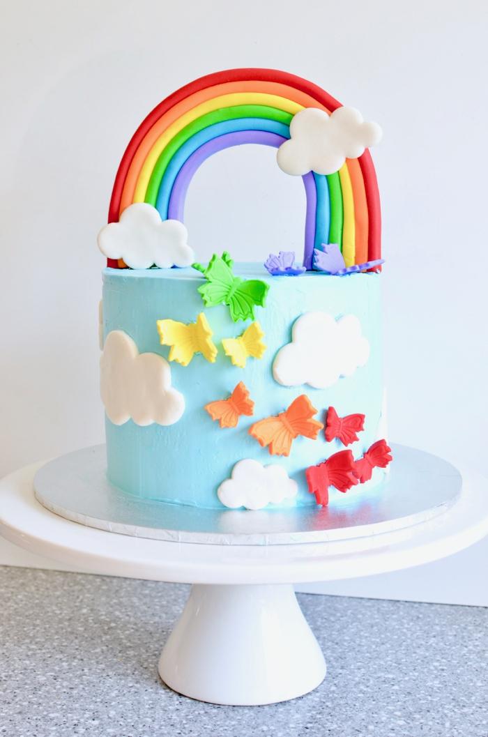 comment faire un gateau d'anniversaire arc-en-ciel au glaçage bleu ciel décoré, décoration de gâteau originale de nuages et papillons modelés en pâte à sucre
