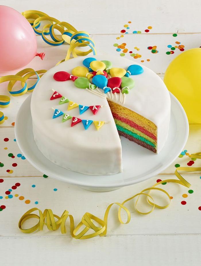 joli gâteau arc en ciel recouvert de fondant blanc et décoré avec des ballons et des guirlandes modelés en pâte à sucre